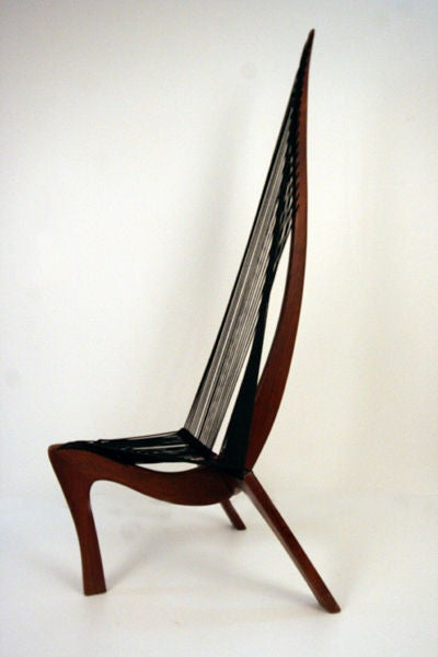 A nice vintage Harp chair was likely designed by Jorgen Hovelskov and manufactured by Christensen & Larsen, Mobelhadvaerk, Copenhagen in 1960s. Its unique form was inspired by a Viking ship bow section. The expertly crafted frame, in solid walnut,