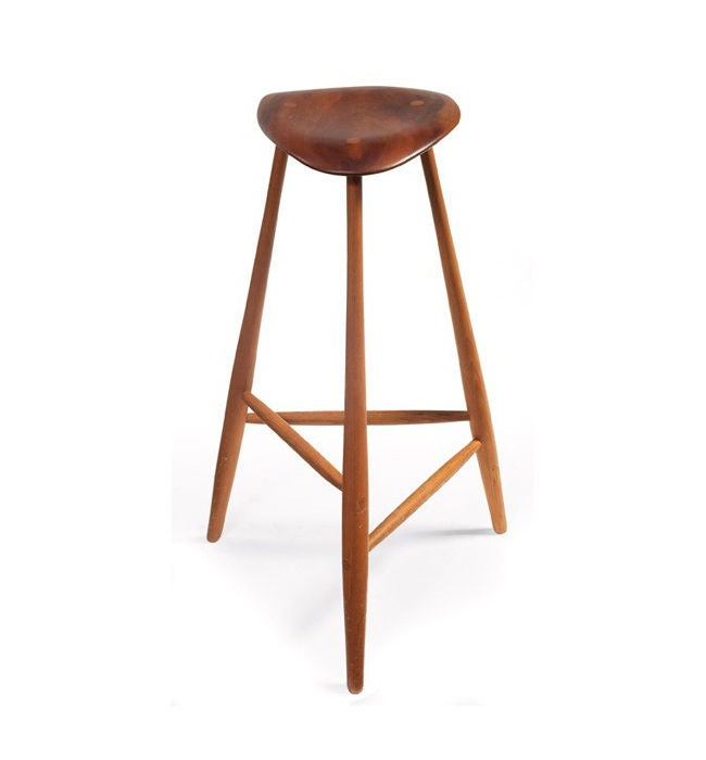 The iconic stool was handcrafted by one of the most celebrated American woodworkers Wharton Esherick in 1966. It features a sculptural free-form walnut seat over three tapered legs of carved oak connected with spindle stretchers. Excellent original
