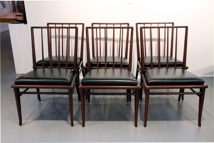 Set of Six walnut dining chairs T.H. Robsjohn-Gibbings for Widdicomb. Vertical slate back with subtle architectural silhouette is further complimented by the slightly flared front legs. Thick cushions covered with black stimulated leather. Newly