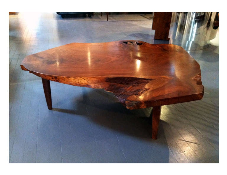 A rare coffee table custom-crafted by George Nakashima in his New Hope Studio circa 1977. It features an impressive thick American black walnut plank top with free edges all around, beautiful grains and sap holes and edges. Its contoured shape is