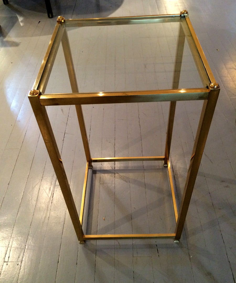 A minimalistic side or end table by John Vesey (1924-1999), who pioneered into using industrial material to re-interpret classic furniture forms. The table is made of brass with glass top and features subtle finals and shaped feet. Circa 1970s.