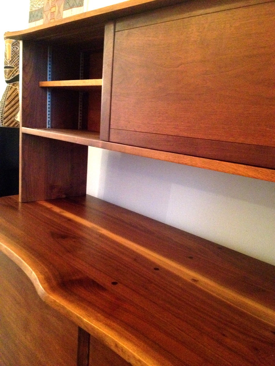 A two-piece custom sideboard pr credenza handcrafted by George Nakashima, circa 1969 in his new hope studio. It is constructed with American black walnut with solid oak interiors. The lower sideboard features a frontal free edge displaying the