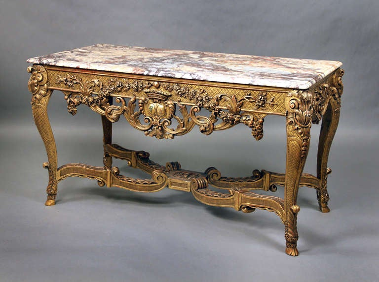 A very finely carved late 19th century Regence style giltwood console.  The shaped rectangular brèche marble-top above a latticework frieze and pierced foliate apron centred by a coat-of-arms, on acanthus-carved cabriole legs joined by a wavy