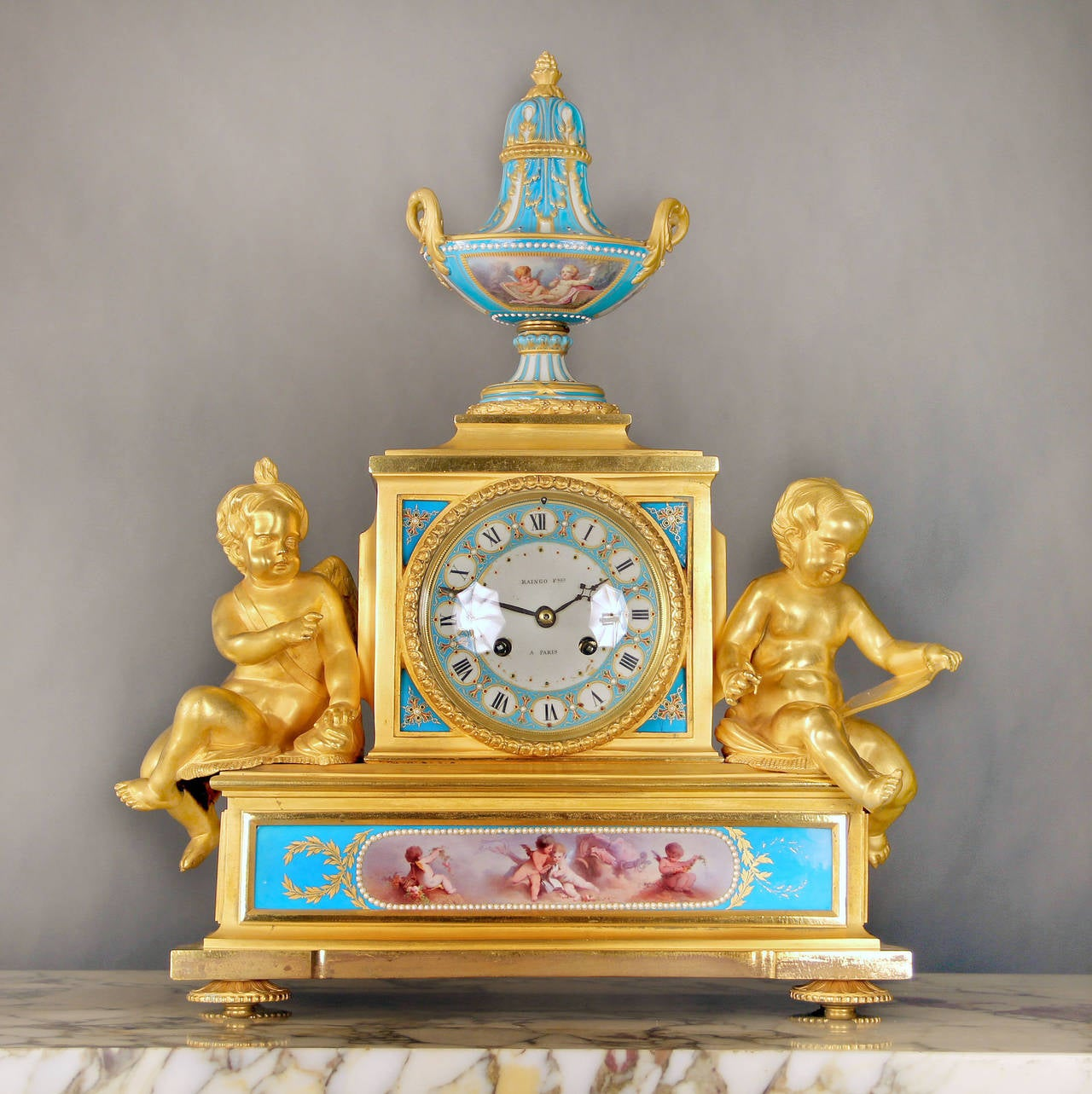 A wonderful and important mid-19th century gilt bronze and turquoise sevres porcelain 'Jeweled' three-piece clock set.  By Raingo Frères.  The clock surmounted by a covered urn with gilt porcelain handles, the clock face signed Raingo Fres A