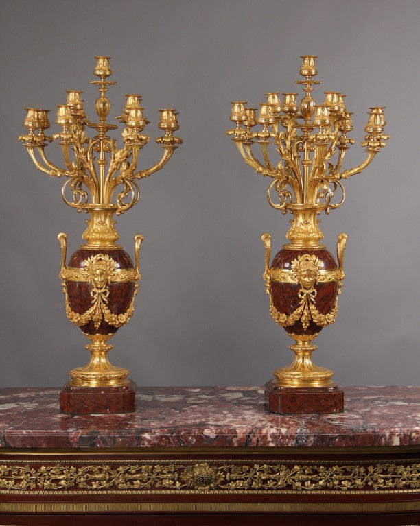 Opulent pair of late 19th century French 13-light candelabra.  Composed of gilded bronze and Rouge Royale marble in the Louis XVI taste, the two-handled vases richly mounted with female masks and floral garlands, the pair supported on thick square