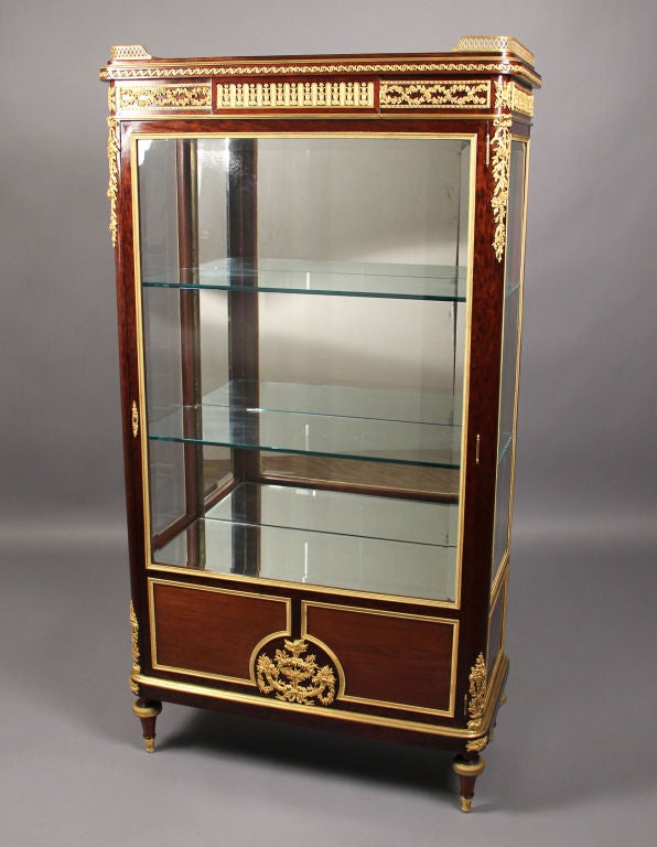A great quality late 19th century Louis xvi style gilt bronze-mounted vitrine.  By François Linke.  The rectangular paneled top with three-quarter gallery, above a conforming entwined garland frieze, over a glazed beveled panel door and central