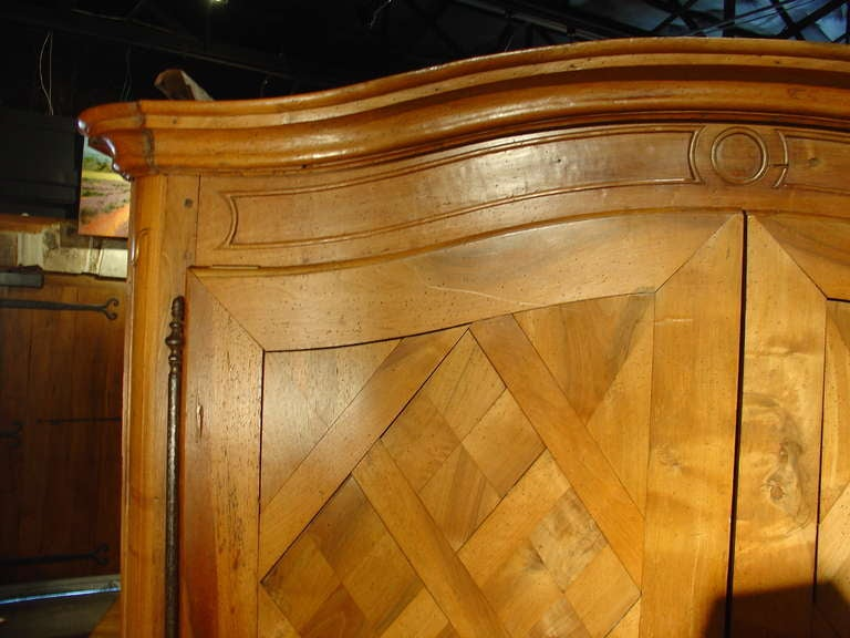 A very unusual parquet armoire coming directly from a home in Brittany. An old ebenist of the area from which this armoire originates is quite confident that this wood was harvested in the Forest of Troncais due to the very few knots visible in the