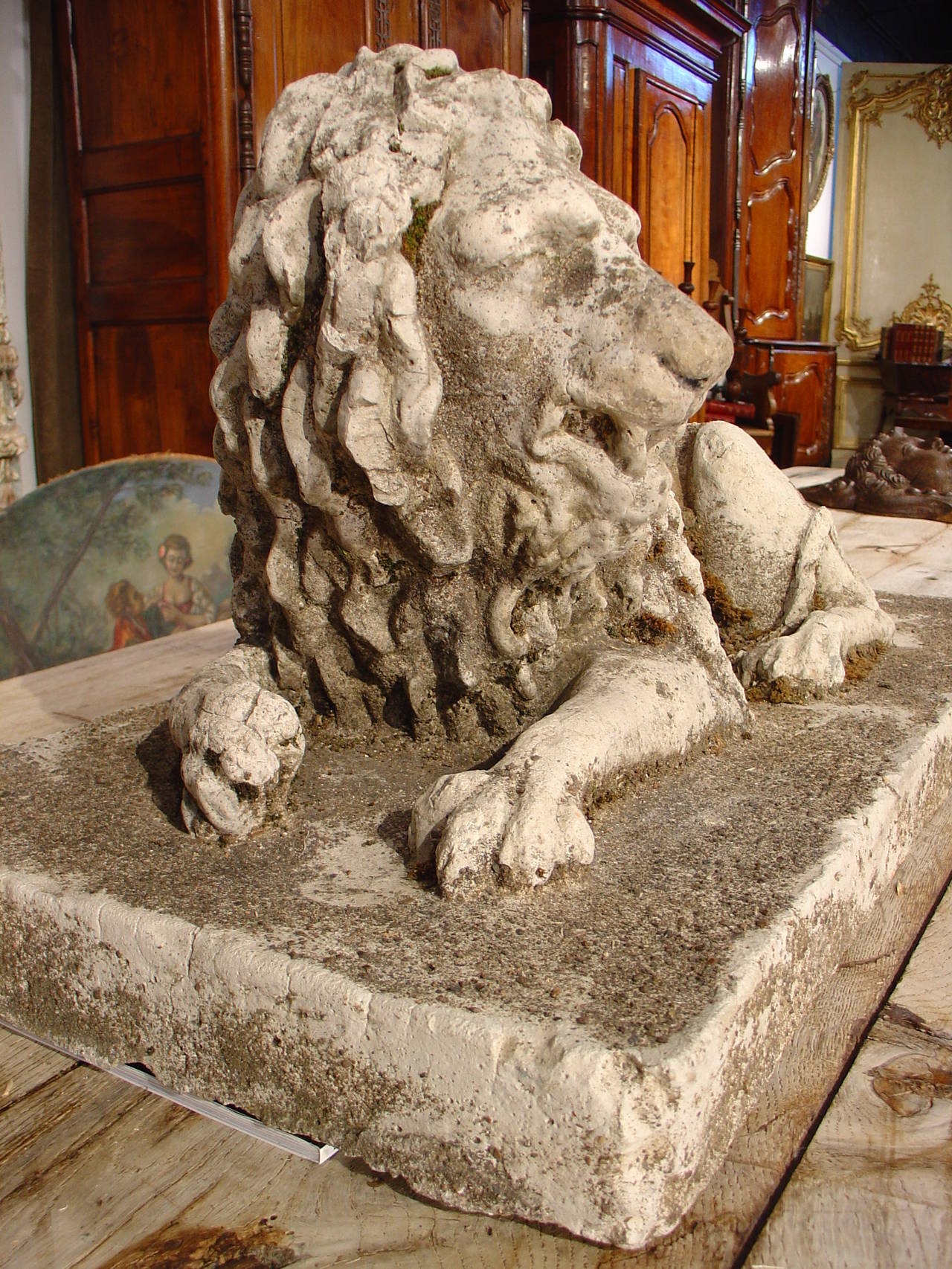 This is a 19th century French reconstituted stone lion statue lying down on a rectangular base. The sculptor who did the original of this statue has portrayed the lion in a reclining position on his right side. His right paw is curled inward and his