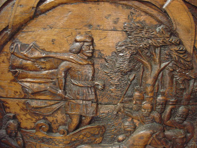 This hand-carved antique French stylized cartouche panel depicts the arrival of an important figure in a chariot drawn by two horses. Soldiers in front of him with a forested background are greeting him. The entire scene is surrounded by stylized