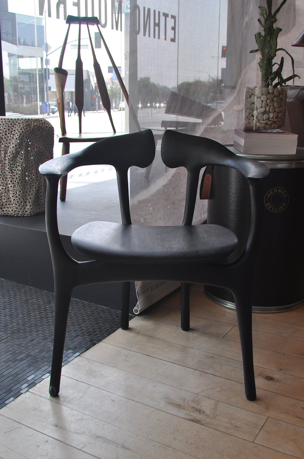 This extraordinary piece is a masterfully handcrafted sculptural work of art. Shown in ebonized walnut frame and seat. Various wood options available. Each piece is signed by the artist.  Made to order.  Custom options available.  Contact Siglo