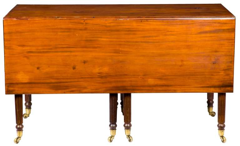 This mahogany table is extremely wide and composed of solid mahogany boards of the finest ribbon grain. The leaves are very heavy, and the table was composed two have the two middle legs swing out and support the entire table in a very stabile and