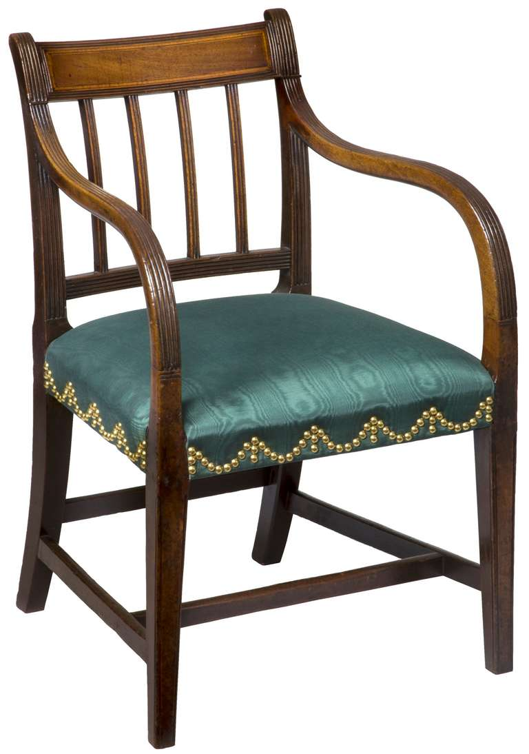 This armchair has beautifully curved reeded arms that gracefully integrate the rear reeded stiles with the front legs. The crest is embellished with highly figured mahogany around a satinwood border with line inlay surrounded by reeding at its edge.