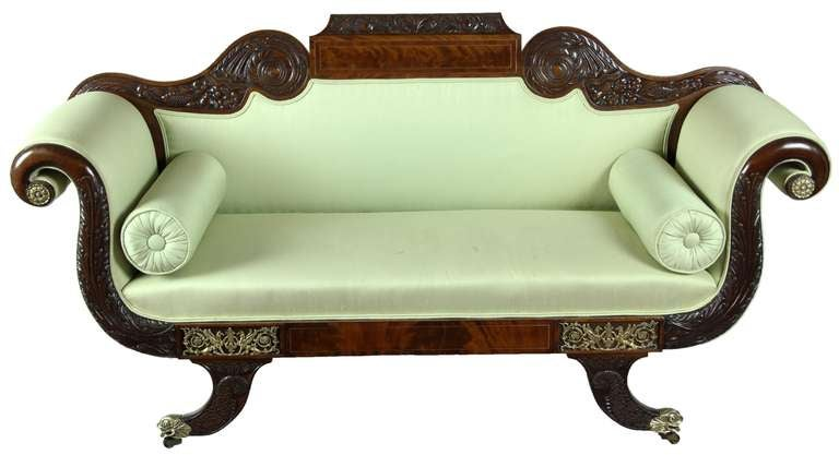 This settee is an absolute knockout. It is a tour de force of the classical motifs of the day, hand-carved and fully embellished. Starting from the top, note the beautiful carved scrollwork cresting a panel of crotch mahogany encased in brass and