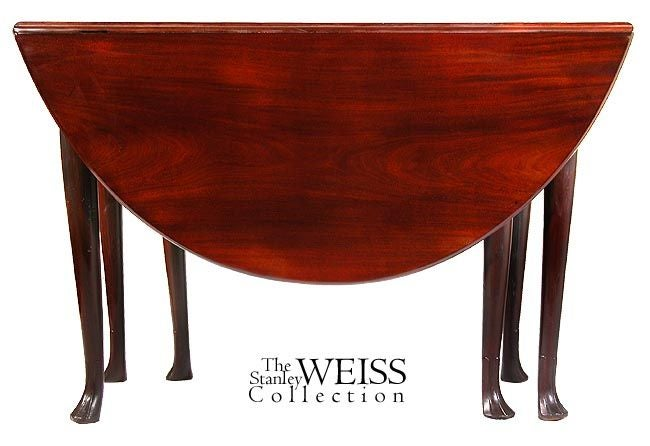 This table is composed of three solid unjoined boards, the top, and two drop leaves. The mahogany is a deep red-brown, with deep figure throughout (see detail). The legs are a very delicate cabriole form ending in carved trifid (stocking) feet.