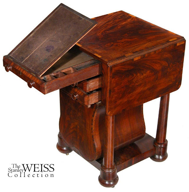 This worktable has an unusual lyre form basket composed of highly figured mahogany, crossbanded with rosewood. The crossbanding element is carried through throughout on the plinth at the base, the drawer edges and on the top, including its leaves.