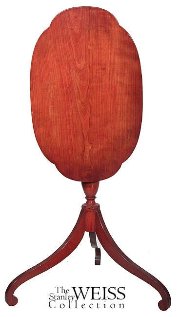 This table has beautiful lines with feet that seem to go on forever. The shaft is a slender baluster form and the top, in general oval form. This is a very delicate table with cherry that has turned an orange or brown color over time.