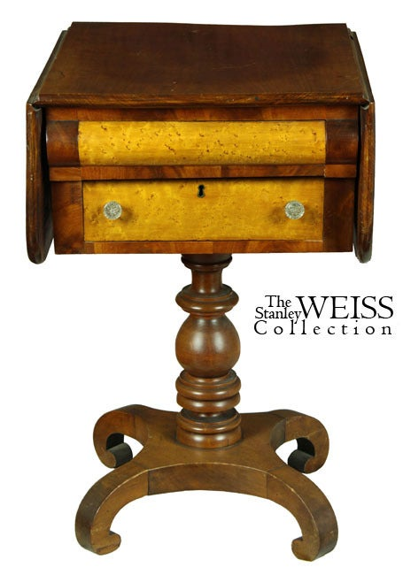 This two-drawer worktable, with side leaves is embellished with bird's-eye maple around a convex upper drawer and flat lower drawer. The base is vigorously turned in a stylized manner, as are the scroll feet, which are diminutive in scroll, yet