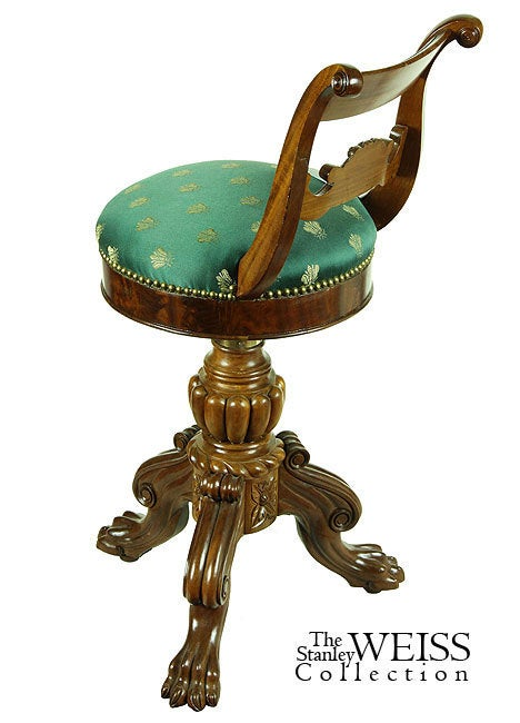 This piano stool distinguishes itself with finely carved embellishments in the swiveling upper seat, with a Classic fruit basket flanked by scroll supports, below a paneled crest rail of figured mahogany which is similarly echoed in the seat apron.