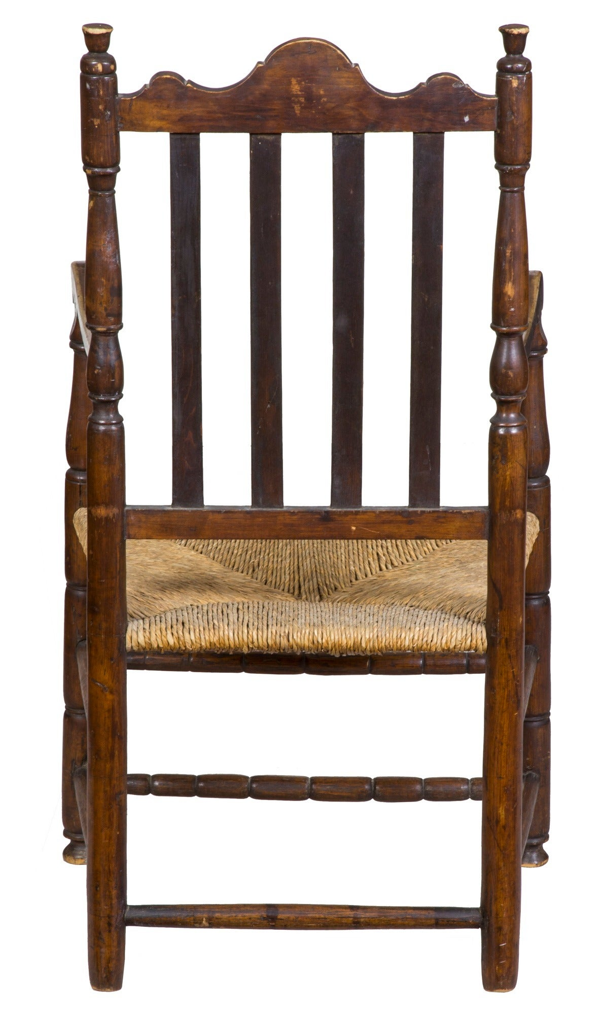 This armchair relates to an example shown in Bishop, the American chair: Three centuries of style (see scan) with reeded vertical slats on the back and the sausage turnings at the base. Unlike the comparative example illustrated, the crest of our