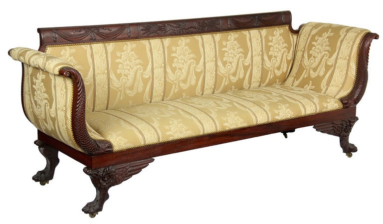This sofa has it all. It retains the finely carved Phyfe tablets that compose the crest rail, and instead of the usual reeded arm supports, finely carved dolphins are employed. Note the deeply carved scales, et al. This certainly is the work of a