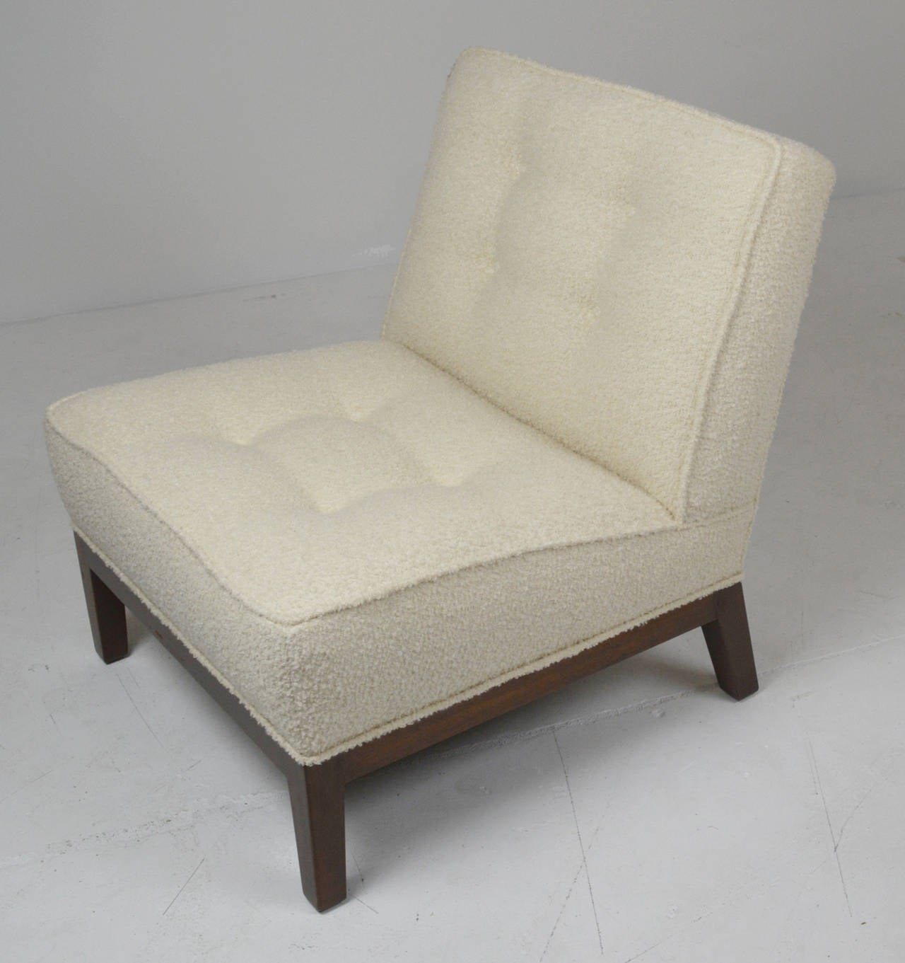 slipper chair by Edward Wormley for Dubar. Button tufted tight seat and back in ivory boucle. Wood base refinished in dark walnut
