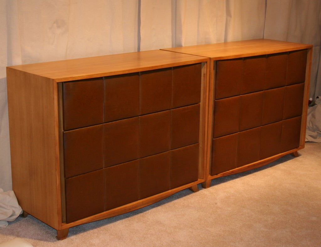 A pair of three drawer chests, designed by Gilbert Rohde for Herman Miller in the the 1930's. Bleached mahogany cabinets with original padded naugahyde drawer fronts. Great detailing, including a slightly bowed top and base and flared legs. Matching