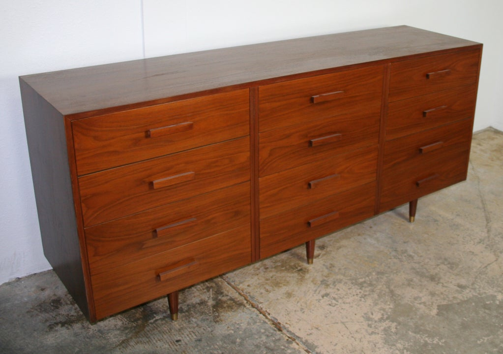 Elegant 12 drawer dresser in walnut with walnut handles. The case floats on three pairs of tapered legs with brass sabot.