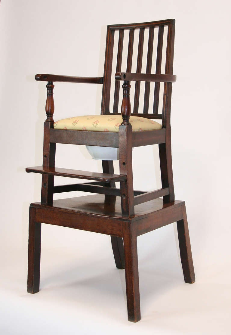 Truly unique convertible English high chair. Chair with cross stretcher wing-bolted to a companion table on four legs. The foot rest can be adjusted in height. Convertible to a table and chair. Upholstered slip seat with original ceramic chamber