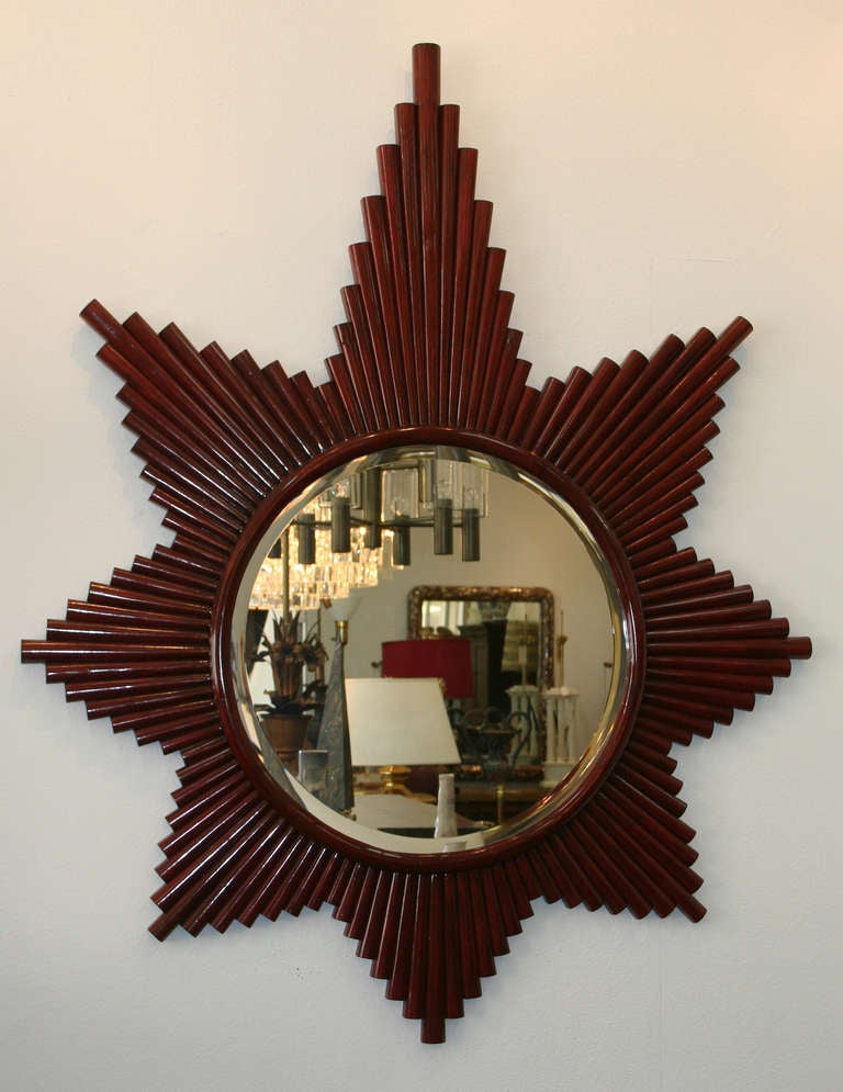 Vintage star mirror comprised of wood reeds surrounding a round beveled mirror. From an Arthur Elrod interior.