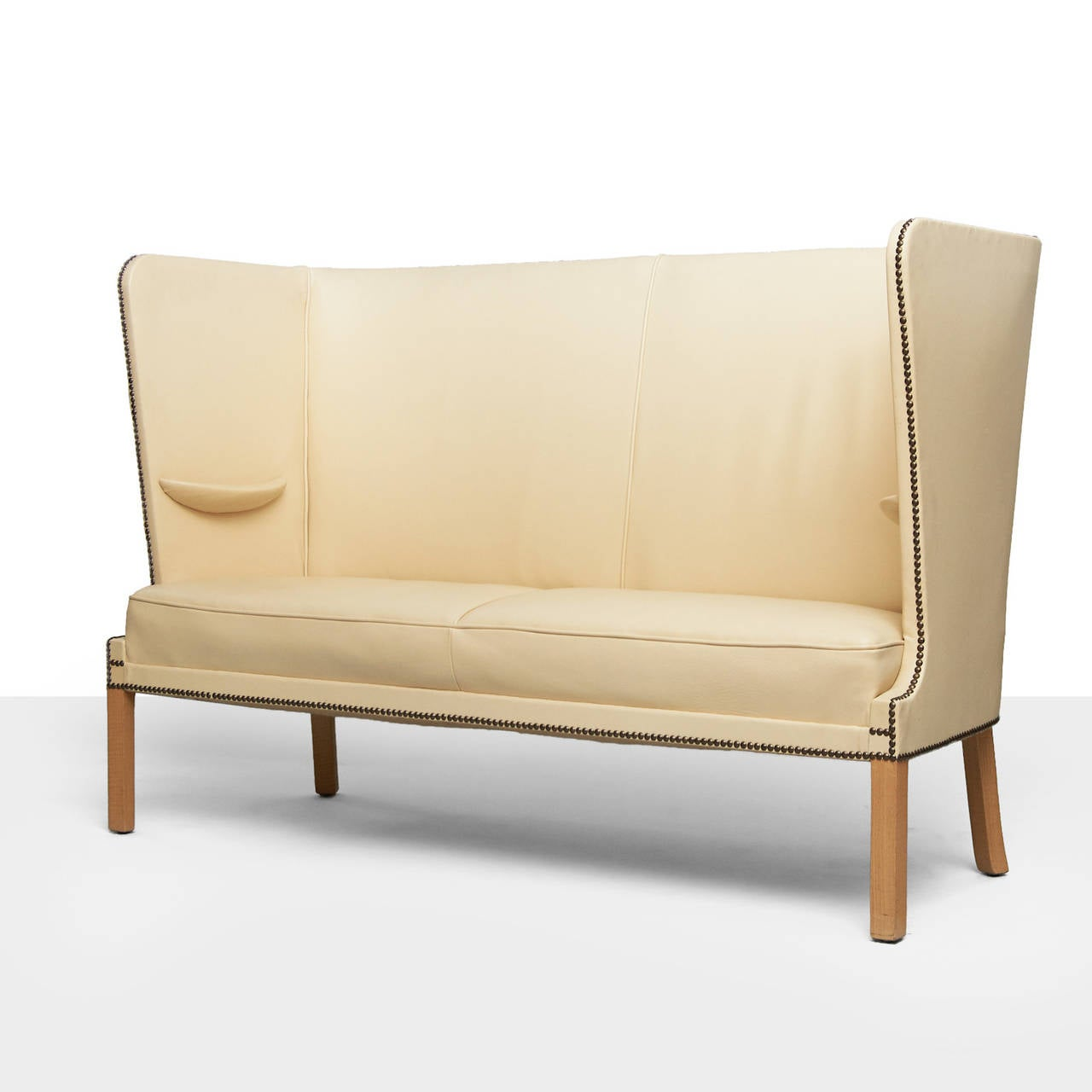 A Frits Henningsen settee of oak and its original ivory leather upholstery with nailhead trim. Features a high wingback and half moon armrests. Designed in Denmark, circa 1940.
