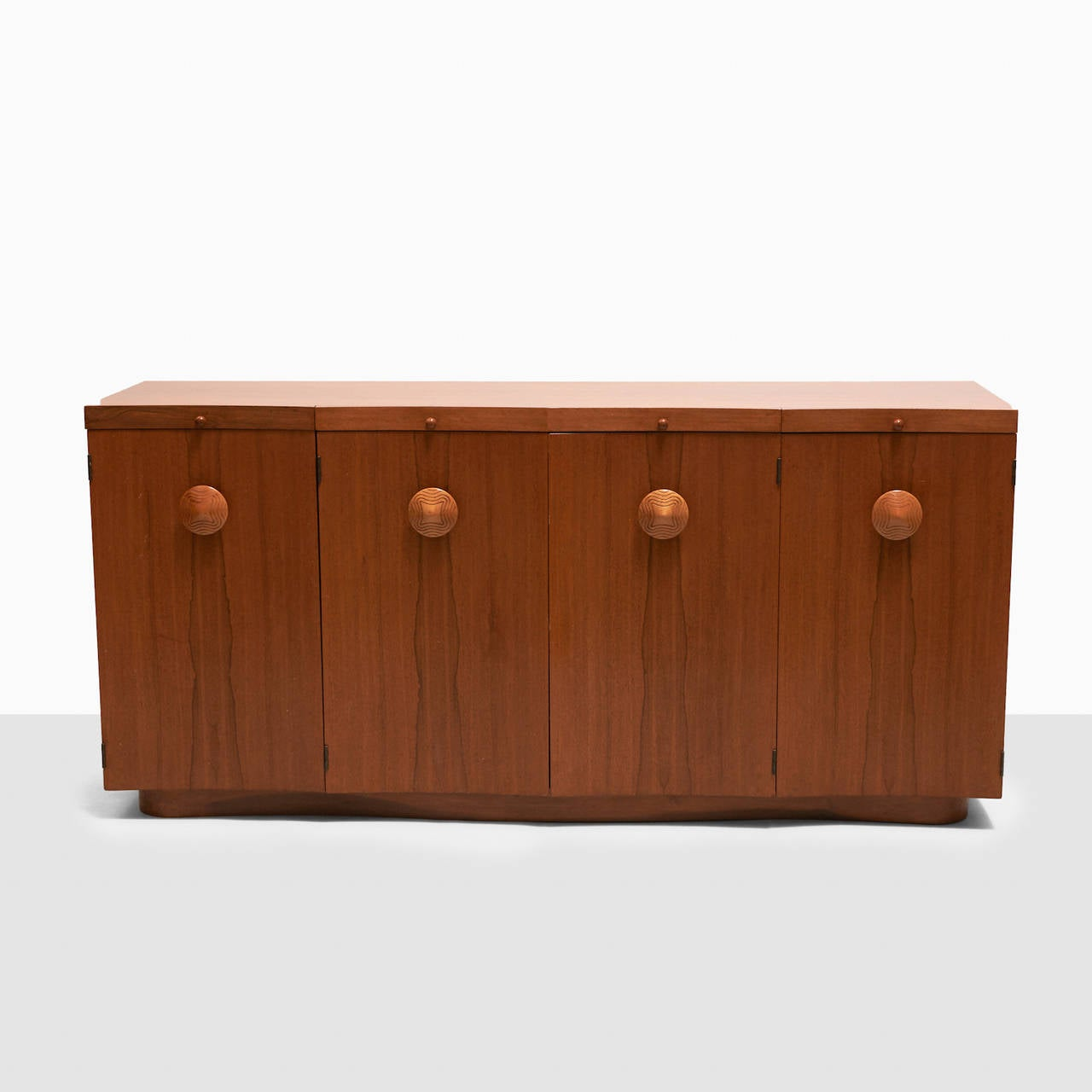 """Gilbert Rohde sideboard from the """"Paldao"""" series. Features a pedestal base, pull-out cutting surfaces and four cabinets with carved nobs. Interior has eight pull-out drawers. Manufactured by Herman Miller."""