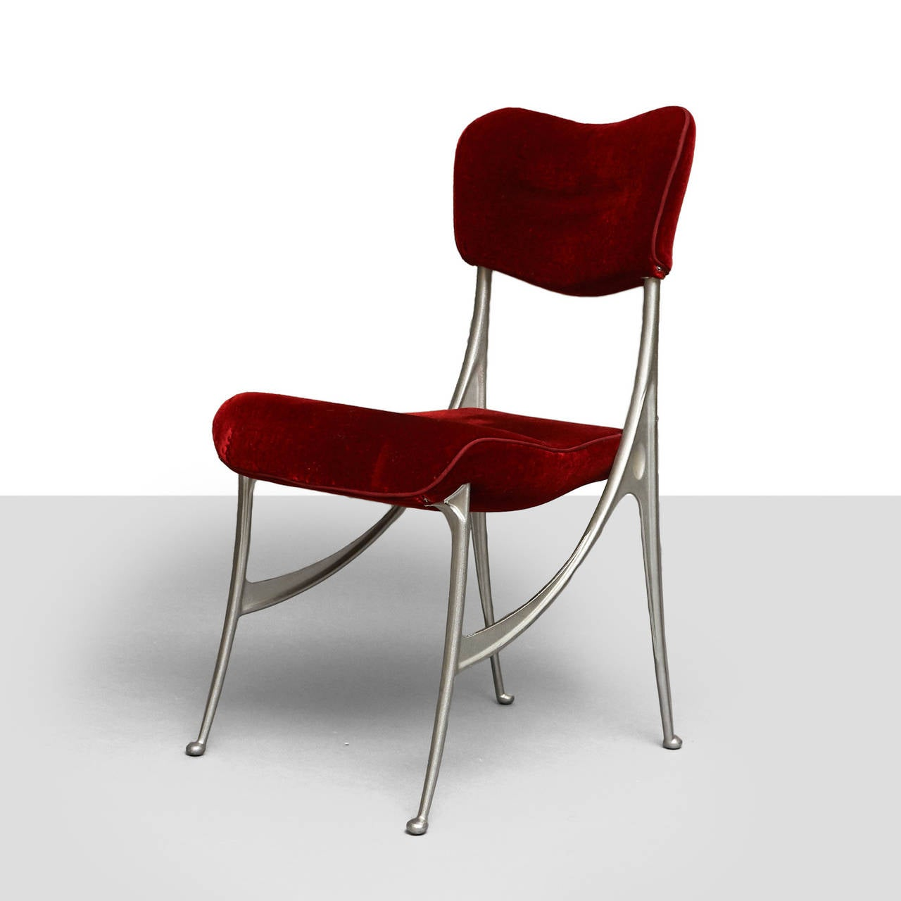 A set of dining chairs by Oscar Tusquets for Driade. Four side chairs and two armchairs with ribbon curl armrests. Curvilinear frame of cast aluminum, covered with red velvet. Designed in 1987.