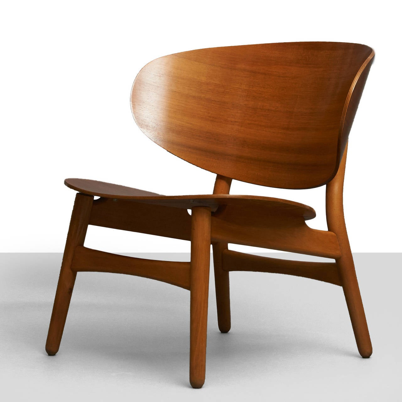 A shell lounge chair by Hans Wegner. Features an oversized, laminated teak back and a maple frame with tapered legs. Retains original label.