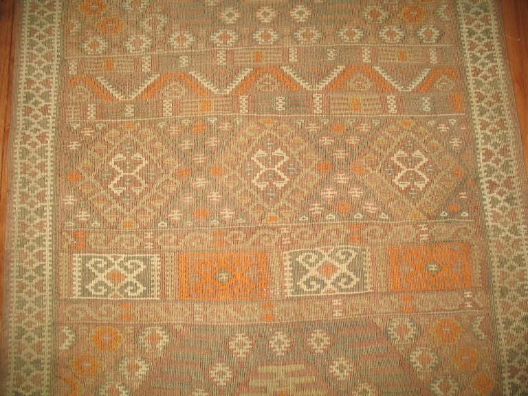 A Mid-Century Moroccan Kilim flat-weave in predominant cream and orange tones.
