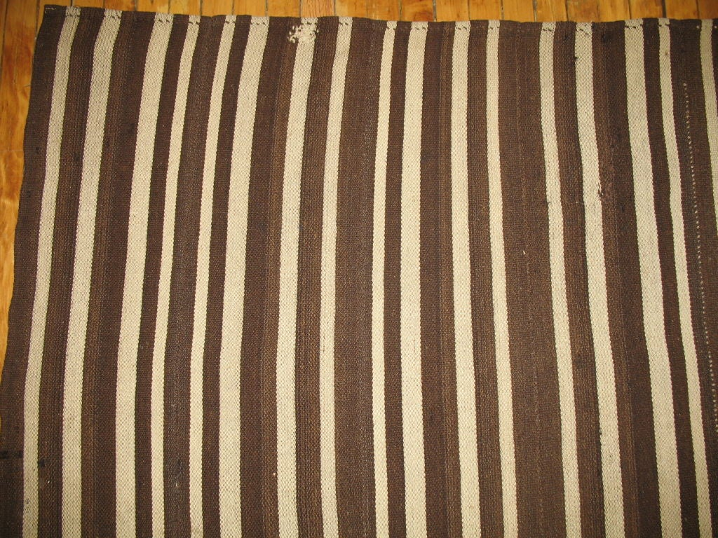 A striped Kilim woven in Turkey. Chocolate brown and creams.