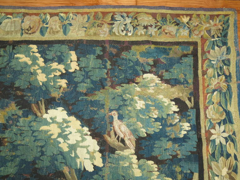 A large Flemish verdure tapestry from the 18th century, featuring a tranquil scene in a woodland setting, with stately trees at right and left in the foreground, with an exotic bird resting in the grass beneath their shadow, and further trees in