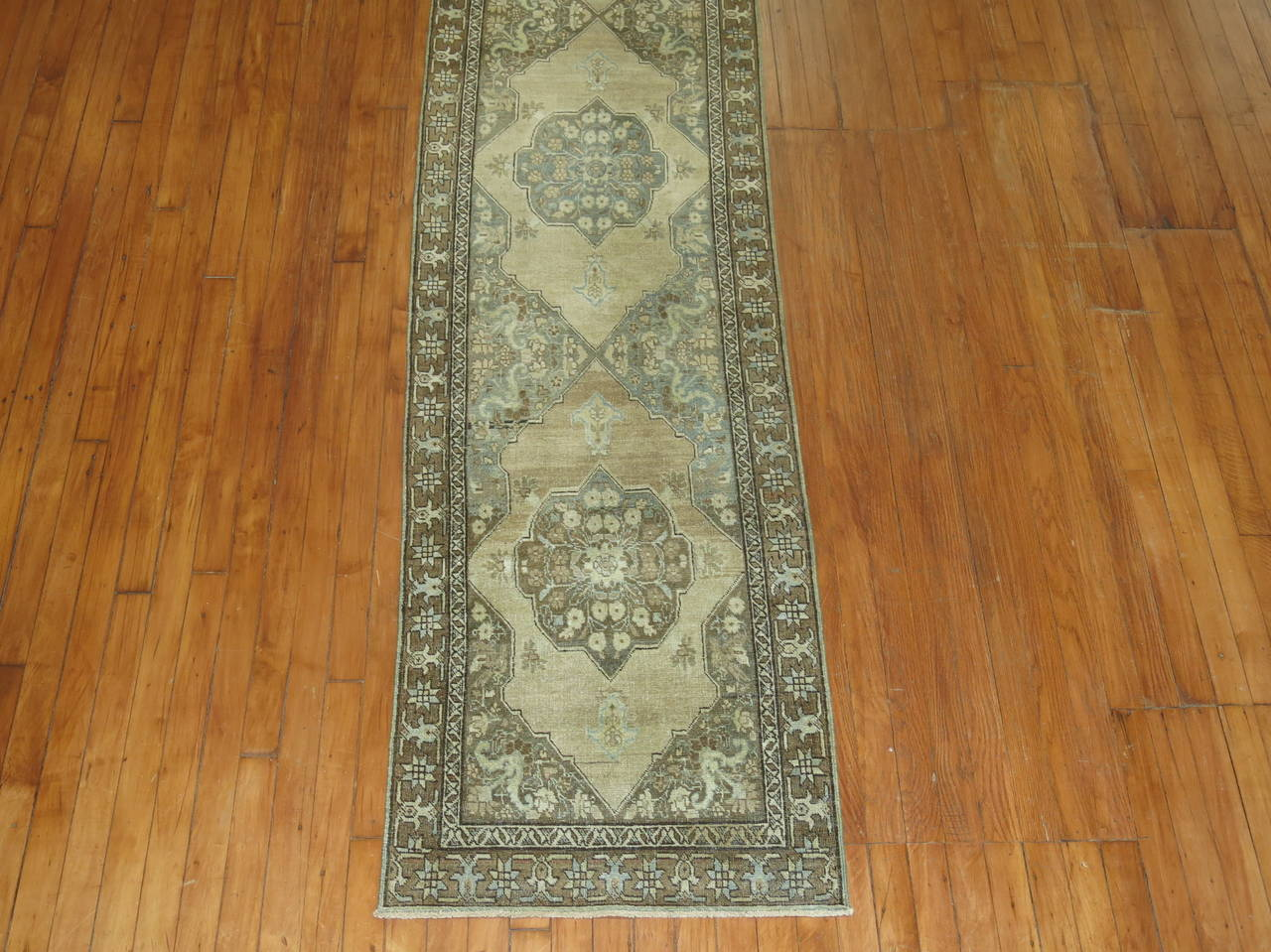 A narrow and long Persian Tabriz runner in browns and caramel.
