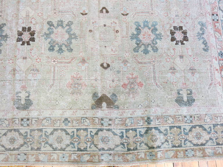 An early 20th century Persian Tabriz with a light gray background, sea foam green and gray with hints of pink.