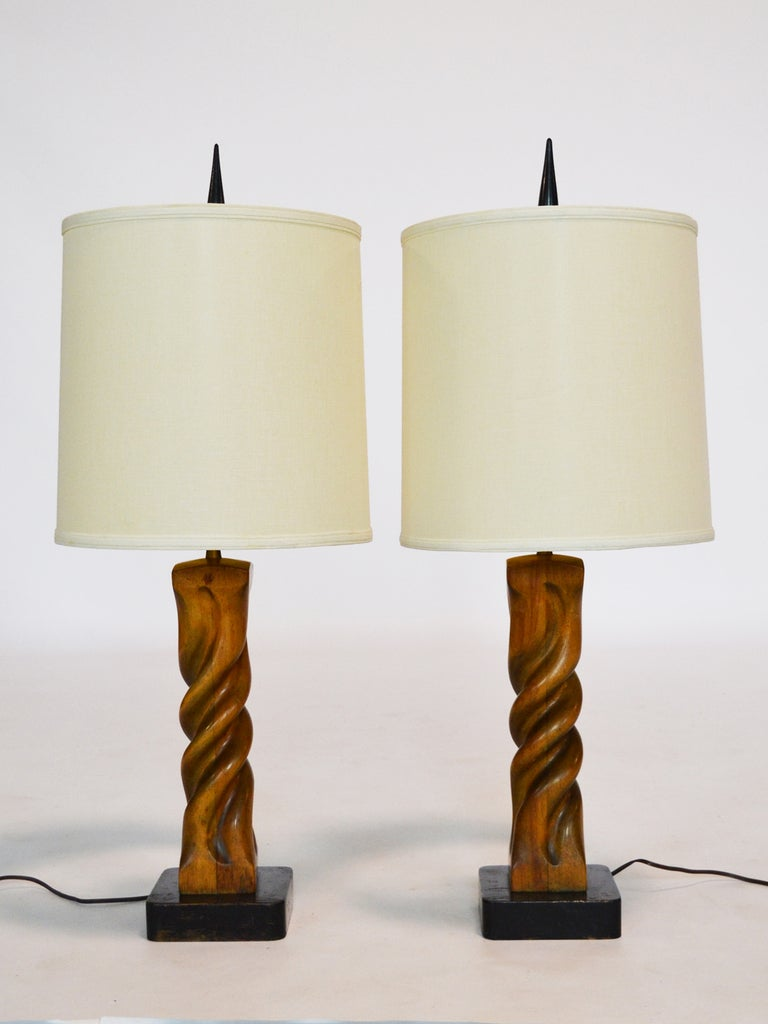 This fantastic pair of carved wood table lamps by Heifetz are fantastic examples of the woodworker's designs. The bases are caved to appear as though they have been twisted 360 degrees. There are mounted on black lacquered bases that are marked