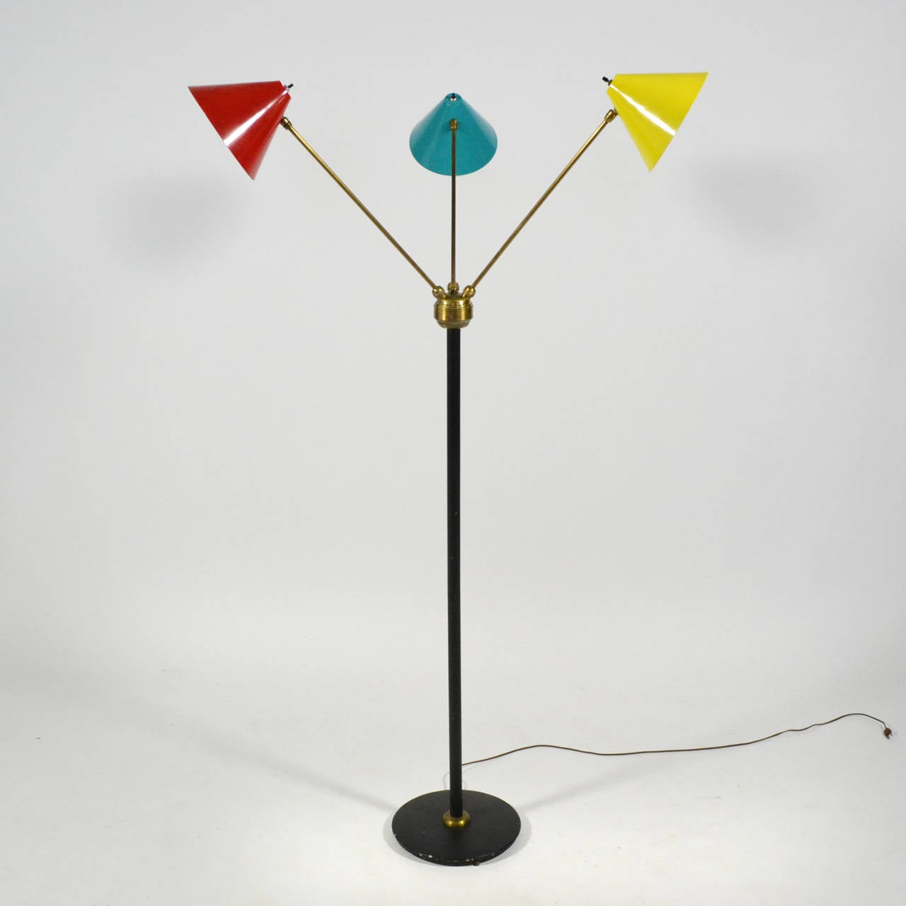 A wonderful example of Italian midcentury lighting, this three-arm floor lamp has conical-shades in red, yellow and blue attached with brass arms to a black central stem and base. With great versatility, the lamp offers a wide array of lighting