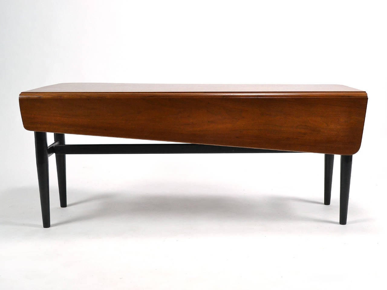 This terrific example of Finn Juhl's unique aesthetic is also a highly functional and versatile table. The walnut top has an asymmetrical shape and a drop leaf on one side. Exquisitely constructed and finely detailed, the cabinetmaker quality