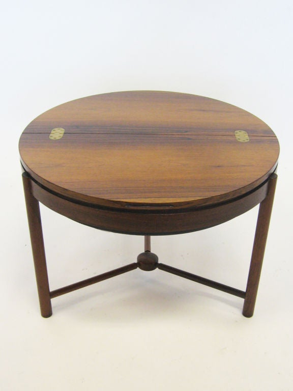 This handsome little table was designed by Rolf Rastad & Adolf Relling to hold sewing supplies, but the rotating shelf under the flip-top serves just as well to hide playing cards, ash trays, coasters or other small items. Finely crafted by Rasmus