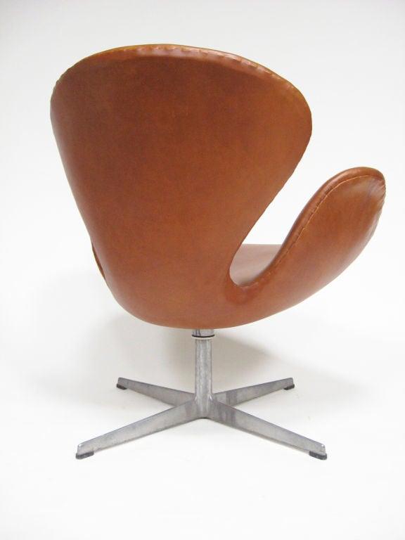 Aluminum Arne Jacobsen swan chair in cognac leather by Fritz Hansen