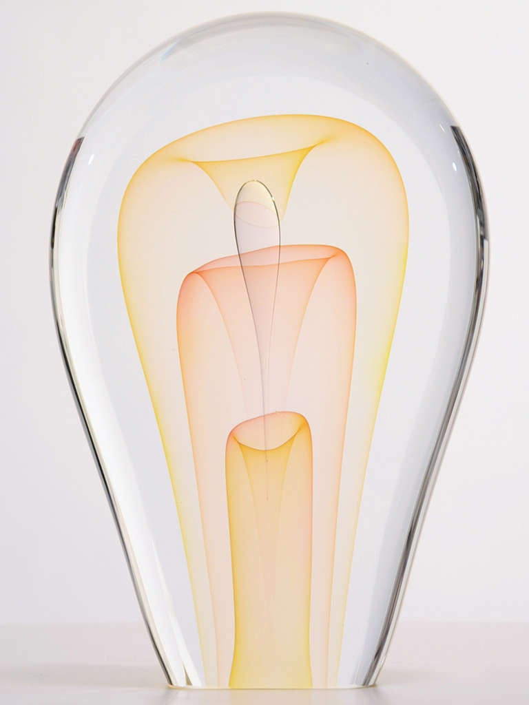 American artist Ed Nesteruk (b. 1941) is known for his delicate and brilliantly executed sculptures in glass. This piece shaped like a flattened upside-down teardrop in clear glass and is internally decorated in gold, pink and clear forms which