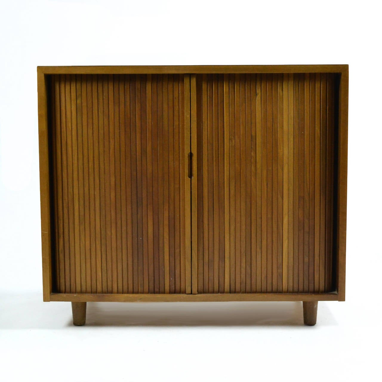 From a series of case goods designed for Glenn of California by Milo Baughman, this handsome walnut chest features two tamboured doors which conceal three drawers with bittersweet red drawer fronts, and a pull-out shelf perfect for folding and