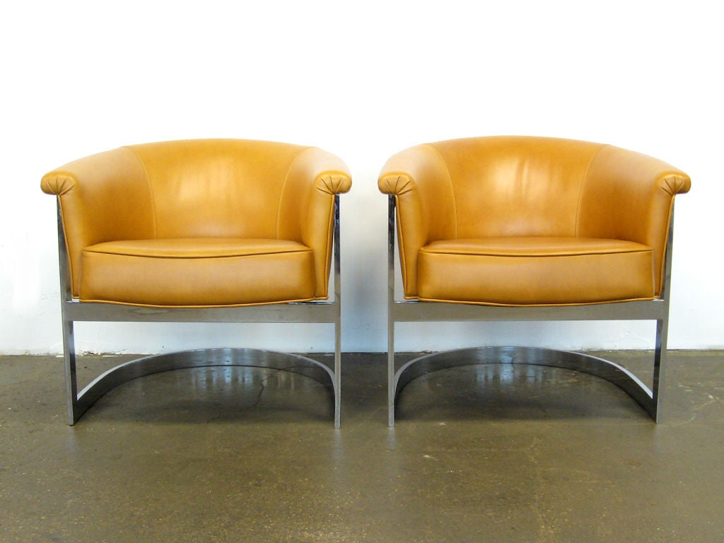 This handsome pair of lounge chairs by Milo Baughman are incredibly well made with heavy steel frames that cradle the cantilevered seats. Newly upholstered in cognac colored leather.