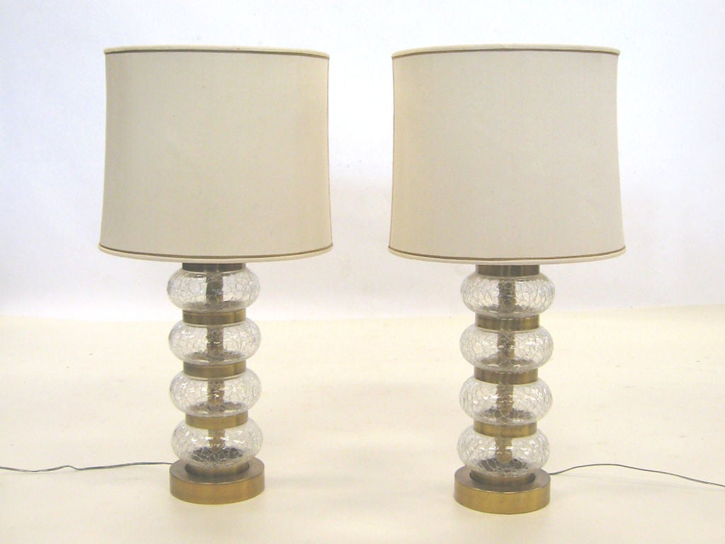 This handsome pair of lamps by Paul Hanson feature shimmering crackle glass orbs separated by brass dividers. Milk glass diffusers support the shades.