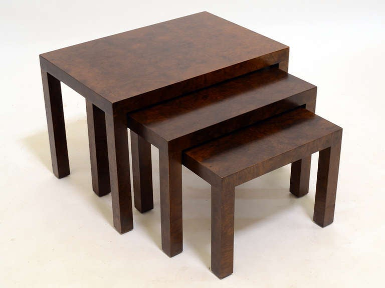 The designs Milo Baughman created for Directional in the 1970s often employed simple shapes clad in exotic materials like the rich burled wood on these nesting tables. This set of three tables have a dark finish giving the unadorned parson table