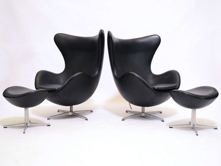 Arne Jacobsen's egg chair is an important icon of modern design. This matched pair in black leather have the tilt function and matching ottomans which exponentially increase the comfort.