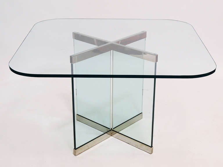 A very refined design, this dining table By Leon Rosen has a glass base in an X-form with chrome fittings at the top and bottom which maintain the shape and protect the glass from chipping. The square glass top has softly radiused corners, and like